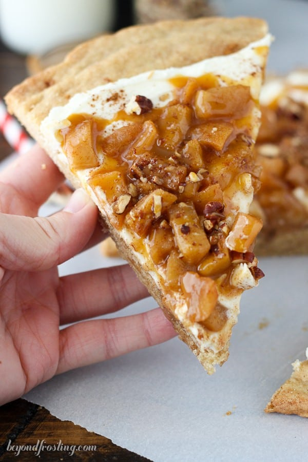 Enjoy fall with Apple Pie Dessert Pizza. It's a giant snickerdoodle cookie topped with vanilla marshmallow buttercream and homemade apple pie filling. It's finished off with plenty of caramel. Dessert pizza is the best pizza.