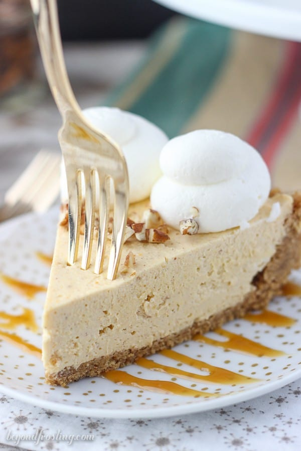 a gold fork sinking into a slice of pumpkin on a plate drizzled with caramel