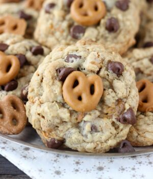 Salty oatmeal cookies with a ribbon of caramel, chopped pretzels, chocolate chips and a salted caramel coated pretzel on top.