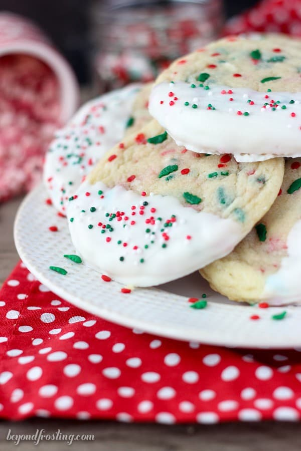Plate with white chocolate dipped sugar cookies topped with Christmas sprinkles.