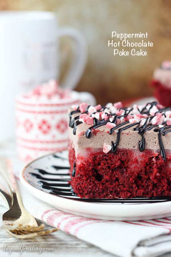 This festive Peppermint Hot Chocolate Poke Cake is everything you need for your holiday dessert. A peppermint red velvet cake soaked in a white chocolate pudding and topped with hot chocolate whipped cream.