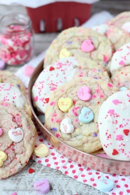 Tell someone you love them with these Conversation Heart Sugar Cookies. These buttery sugar cookies are filled with little pops of sweetness with crushed candy hearts and sprinkles.