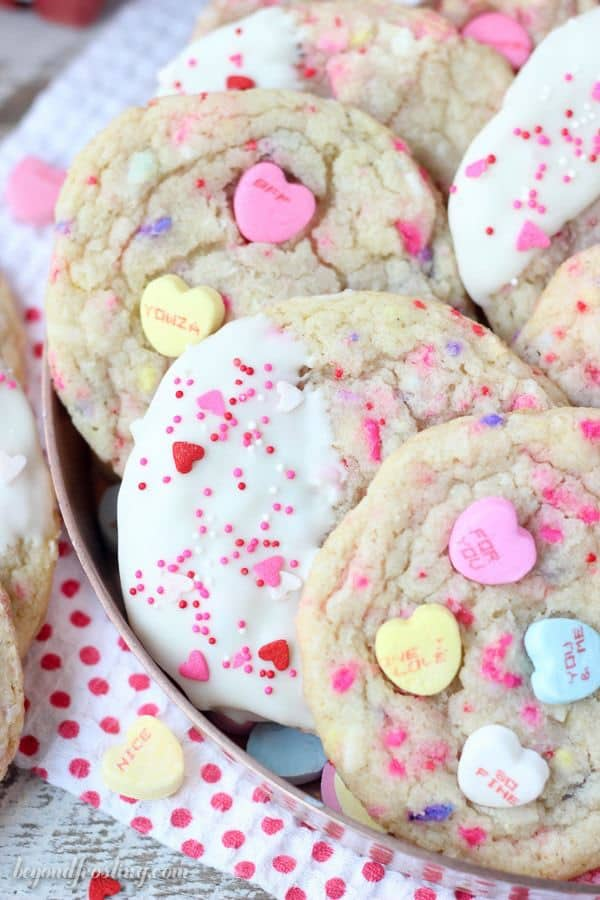 An overhead shot of sugar cookies decorated for Valentines day. Some have conversation hearts and some are dipped in white chocolate with sprinkles
