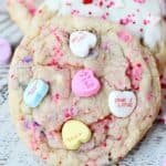 A pretty sugar cookie with pink sprinkles and conversation hearts pushed into the top