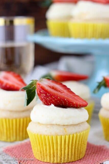 Easy Mimosa Cupcakes in yellow liners topped with fresh halved strawberries.