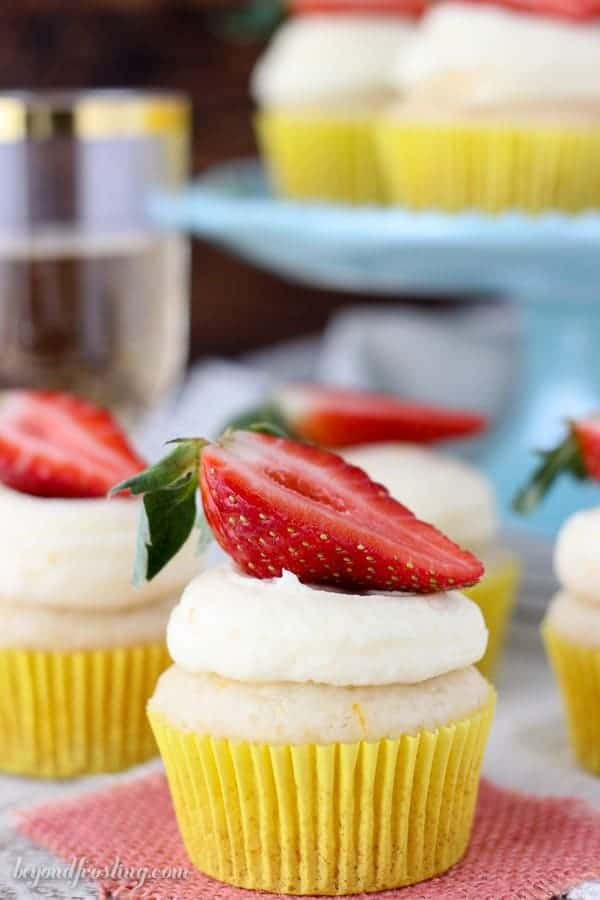 These Mimosa cupcakes are an orange infused champagne cupcake made with a cake mix. Then they are soaked in champagne syrup and topped with an orange cream frosting.