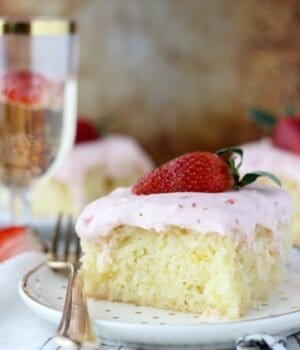 This Strawberry Champagne Cake is an orange infused vanilla cake soaked in a champagne glaze and topped with a tangy strawberry cream cheese frosting.