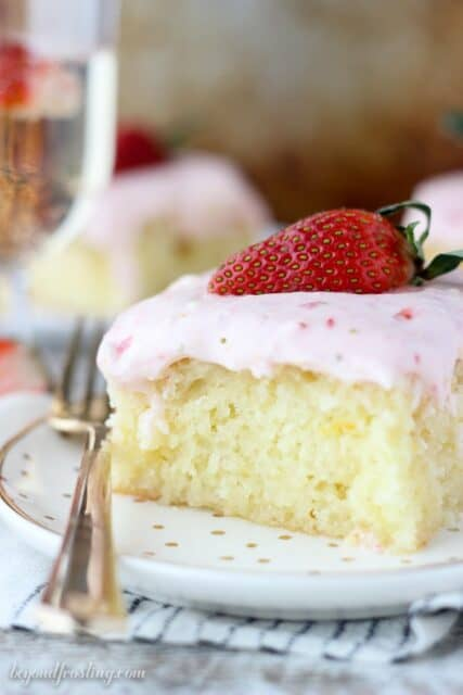 An orange infused champagne cake soaked in a buttery champagne glaze and topped with a strawberry cream cheese frosting. You'll be asking for seconds with this Strawberry Champagne Cake.
