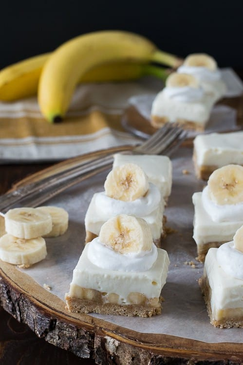 A Platter of Banana Cream Pie Bars Next to Two Unpeeled Bananas