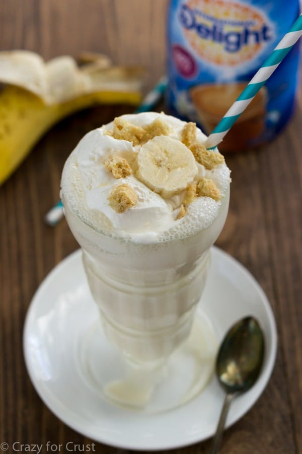 A Glass Filled with a Skinny Banana Cream Pie Milkshake and a Blue Striped Straw