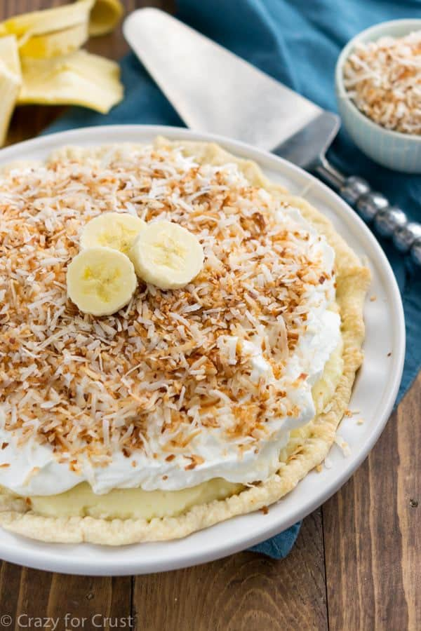 A Coconut Banana Cream Pie on a White Serving Dish on Top of a Wooden Table