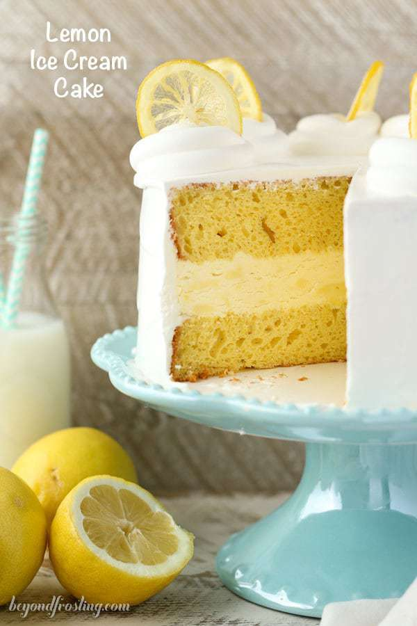 This layered Lemon Ice Cream Cake features two layers of lemon cake with a no-churn lemon ice cream layer sandwiched between them. It's covered in whipped cream and garnished with candied lemons.