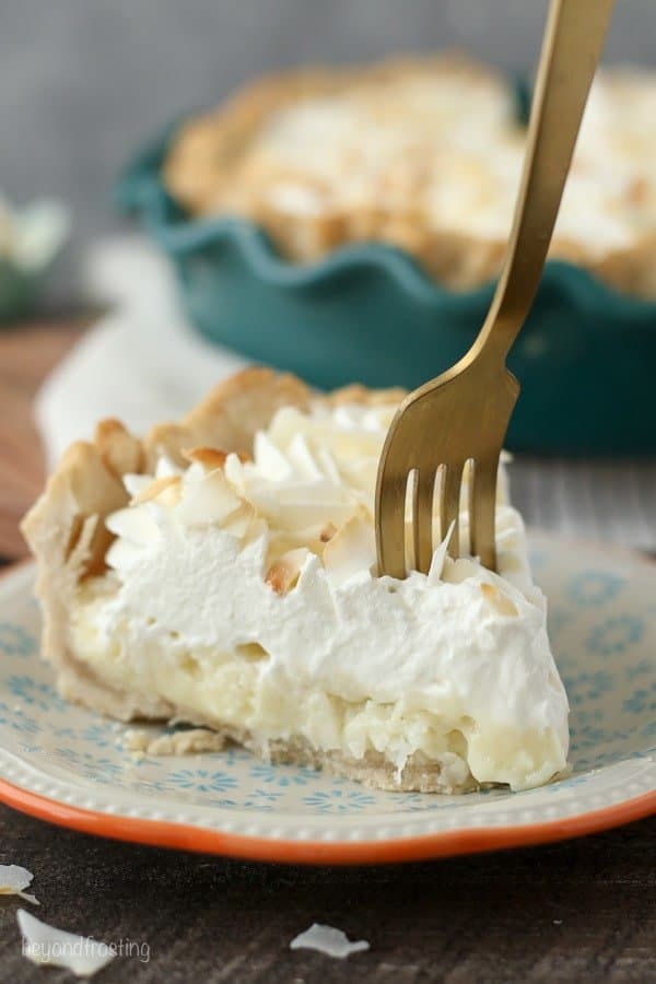 A gold fork sinking into a slice of coconut cream pie