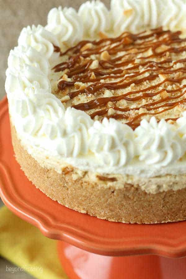 A Banana Dulce De Leche Mousse Cake with whipped cream on top on an orange cake stand