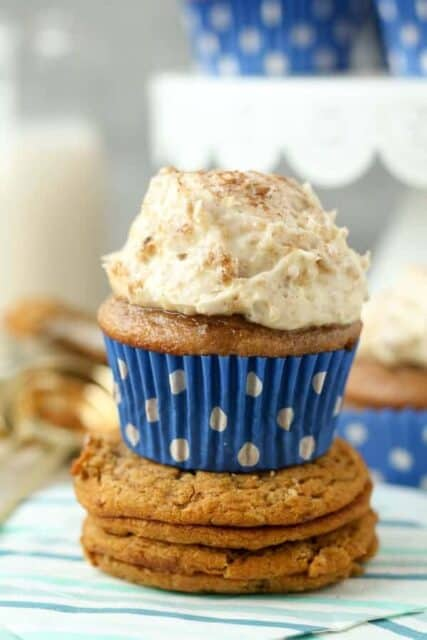 A close up shot of a cinnamon and brown sugar cupcake with a blue polka dot cupcake liner, topped with a big scoop of oatmeal cream pie marshmallow frosting