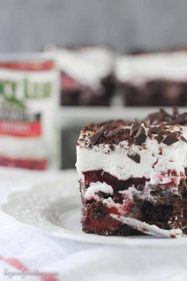 This Black Forest Poke Cake is a gooey chocolate cake filled with hot fudge and cherry pie filling. It is topped with fresh whipped cream and chocolate shavings.
