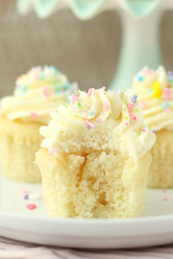 A moist vanilla cupcake with a bite taken out of it and it's topped with a perfect vanilla frosting swirl.