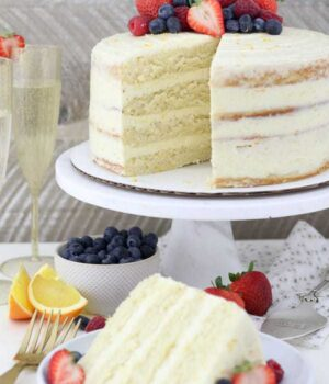 A Slice of Mimosa Cake with Fresh Berries Beside the Full Cake on a Cake Stand