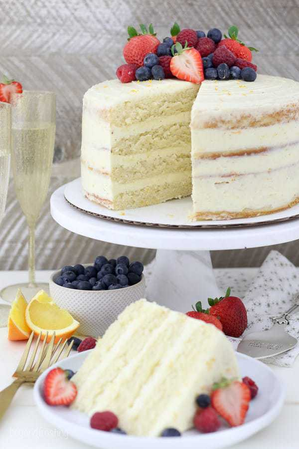 A gorgeous 4 layer cake with an assortment of berries on top, there's a slice missing showing the inside of the cake