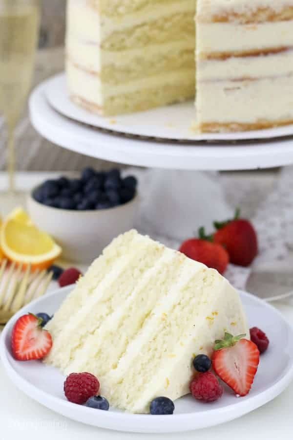 A gorgeous slice of cake on a white plate with berries on it
