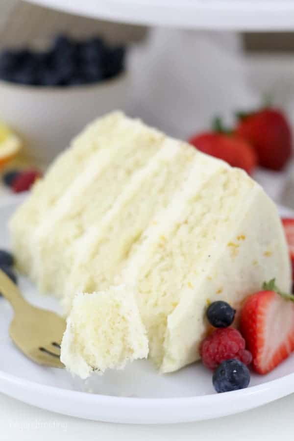 A slice of cake with berries, and a gold fork with a bite of cake on it