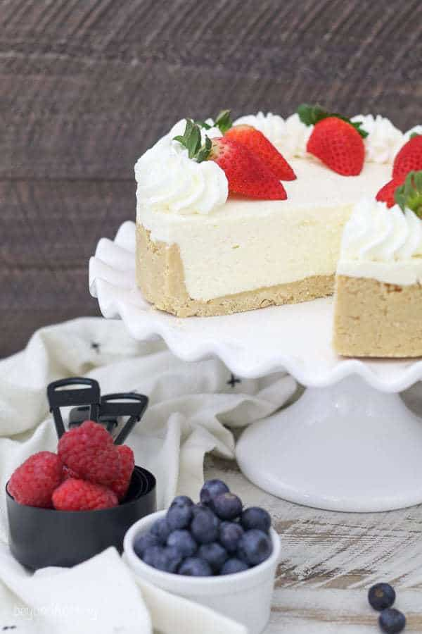 a cheesecake on a white cake plate with fresh fruit