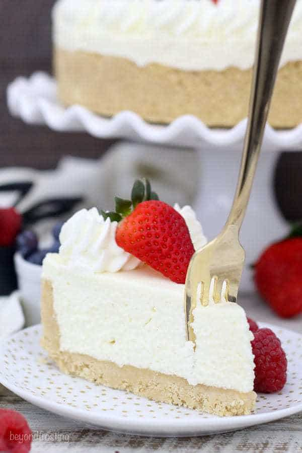 a fork sinking into the top of a slice of cheesecake