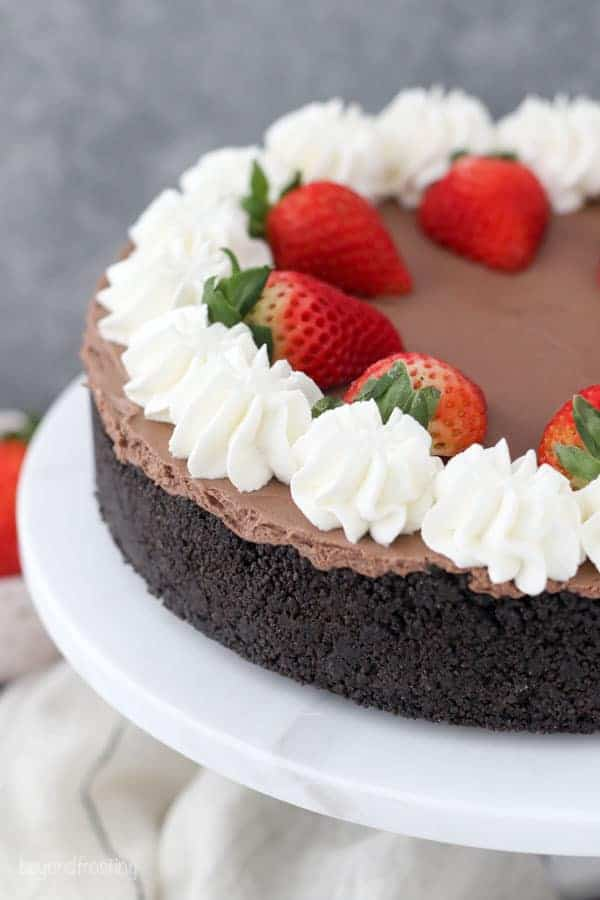 A whole chocolate cheesecake topped with whipped cream and strawberries
