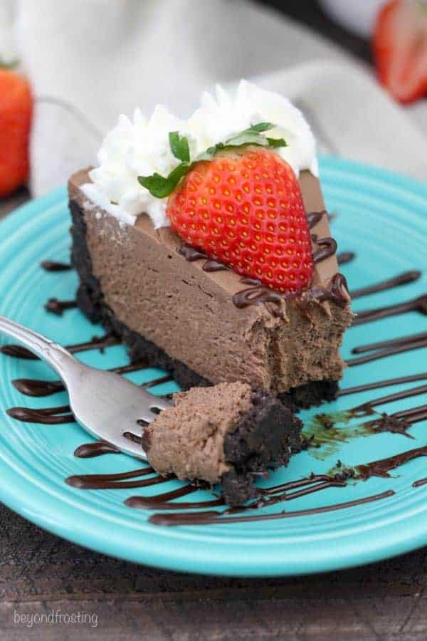 A slice of chocolate cheesecake with a bite taken out of it, topped with strawberries and chocolate sauce