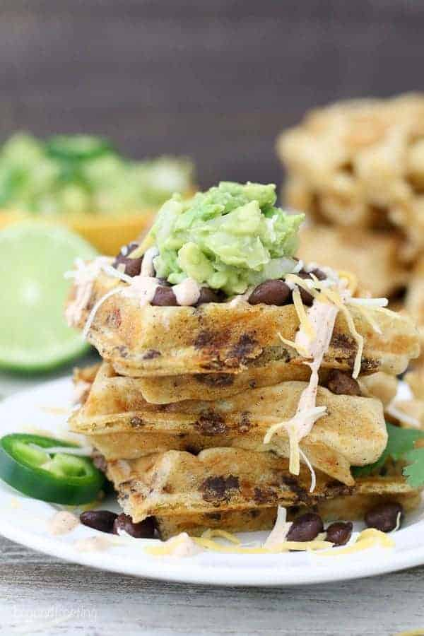 A plate of taco stuffed waffles with guacmole and beans on top
