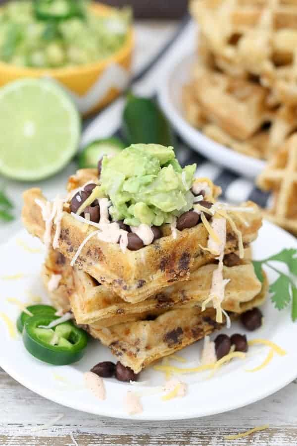 Three savory stuffed waffled on a plate with guacamole on top