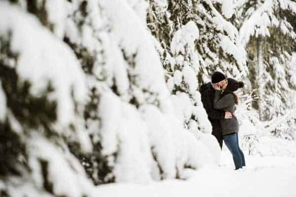 An engaged couple kissing in the snowy woods