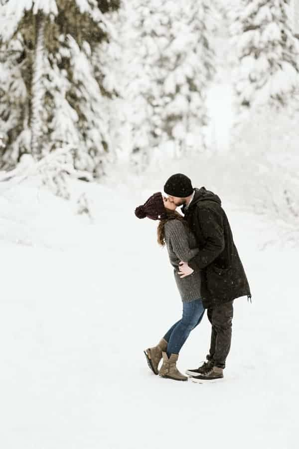 a couple kissing in the snowy wooded area