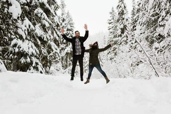 a couple jumps in the air in a snowy scenery