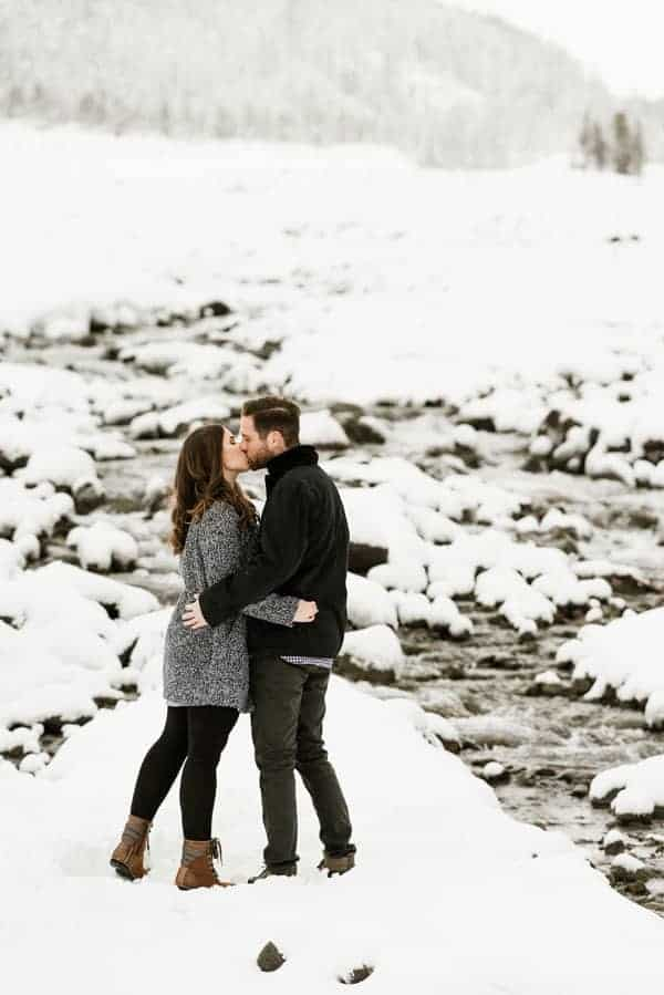 a couple kissing with a mountain backdrop