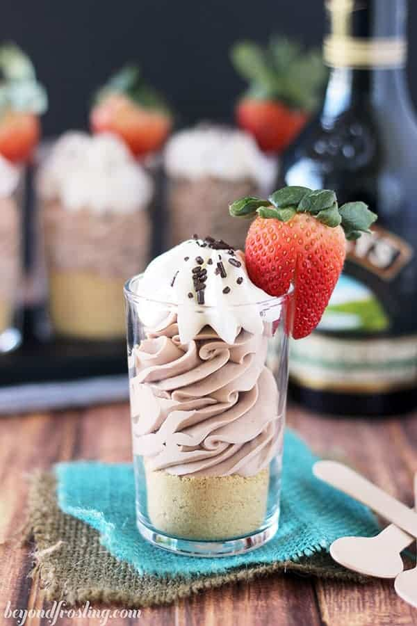 Mini chocolate cheesecake parfaits infused with baileys irish cream and topped with a strawberry
