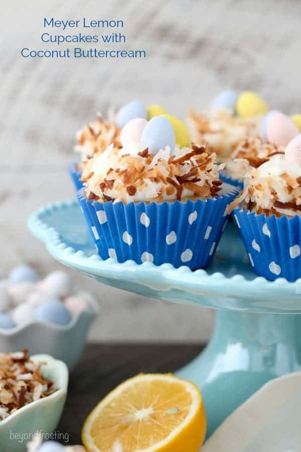 Easter themed Meyer Lemon cupcakes that look like a bird nest with chocolate eggs in the middle sitting on a teal cake plate.