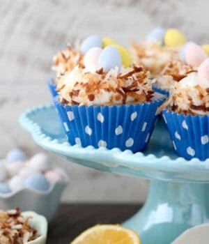 Easter themed cupcakes that look like a bird nest with chocolate eggs in the middle sitting on a teal cake plate.