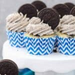 A few Cookie and Cream Oreo Cupcakes sitting on a white cake plate