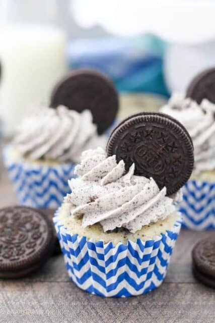 A close up photos of a cookies and cream cupcake with an Oreo buttercream that has an Oreo stuck into the frosting
