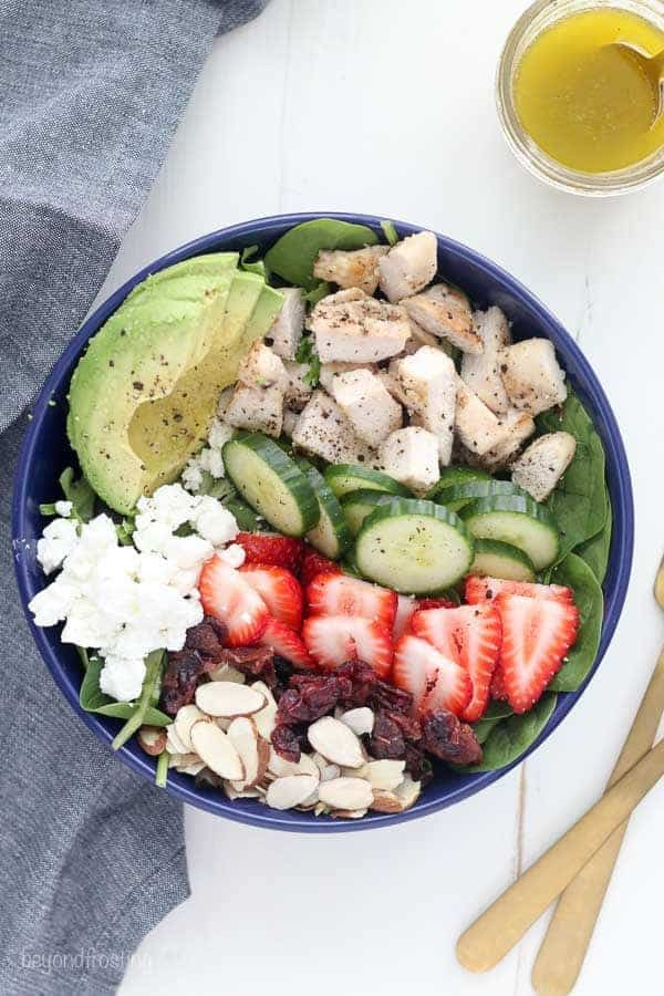 An overhead shot showing the ingredients of the salad including sliced almonds, cranberries, strawberries, goat cheese, cucumbers, chicken, avocado and lettuce. There is a jar of lemon salad dressing in the background and two gold forks.