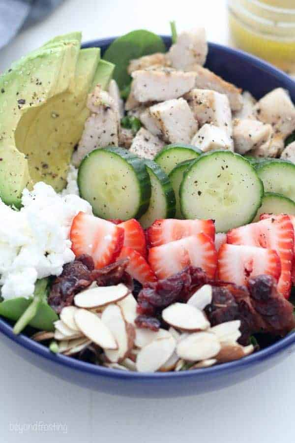 A close up shot showing the ingredients of the salad including sliced almonds, cranberries, strawberries, goat cheese, cucumbers, chicken, avocado and lettuce.