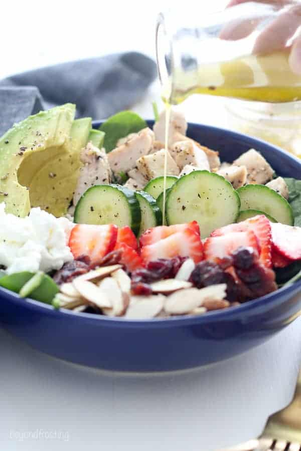 A lemon vinaigrette dressing being drizzled over a strawberry chicken salad.