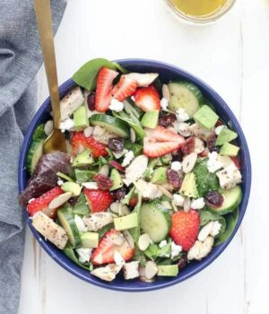 An overhead shot of a tossed chicken strawberry salad in a bright navy bowl with a gold fork hanging out of it.