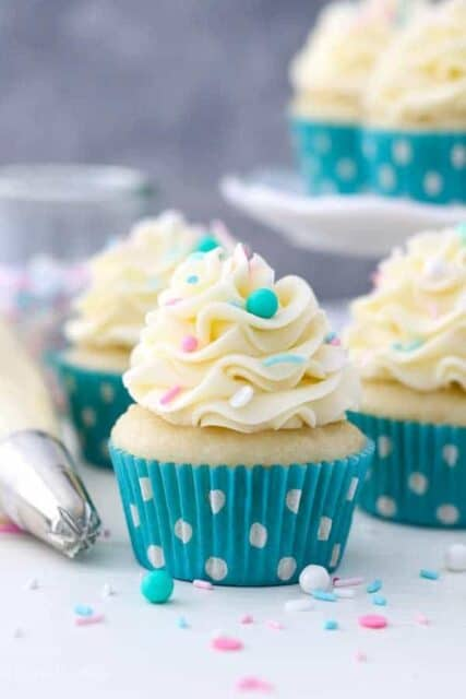 A trip of vanilla cupcakes topped with vanilla buttercream. The cupcakes have teal polka dot liners and pink, white and teal sprinkles.