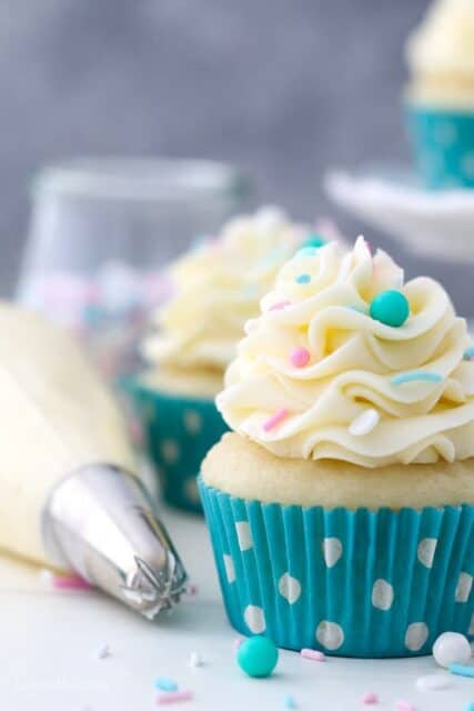 A close up shot of a moist vanilla cupcake with pretty teal sprinkles. There's a piping bag in the background.