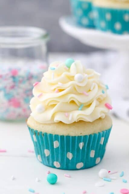 A single vanilla cupcake in a teal polka dot liner topped with beautifully pipped vanilla buttercream and sprinkles
