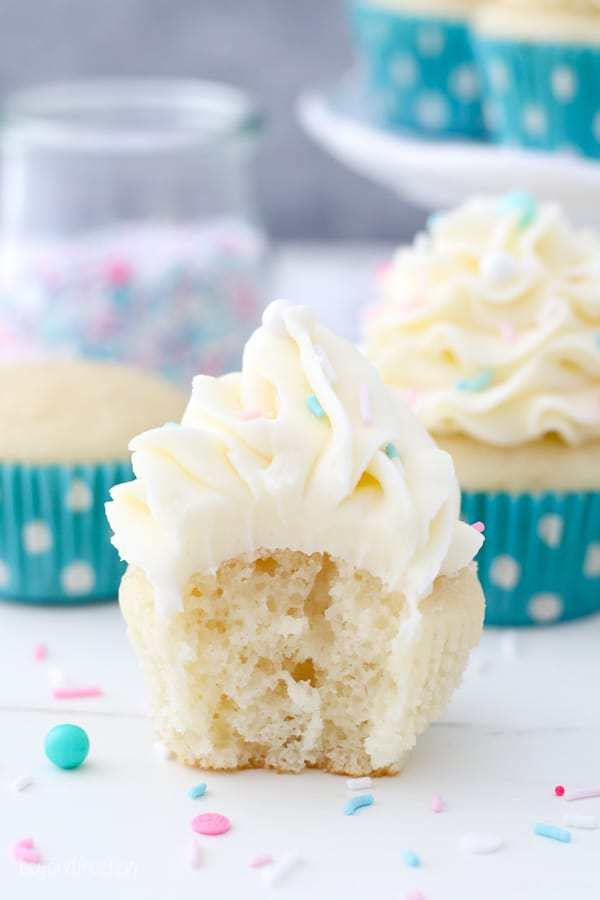 A moist vanilla cupcake with a vanilla frosting and sprinkles has a big bite taken out of it