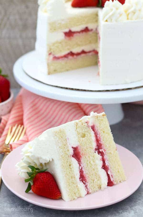 A slide of layered vanilla cake with a strawberry filling and vanilla frosting on a pink plate with a strawberry on top. In the background of the photo is the full cake on a white cake plate.