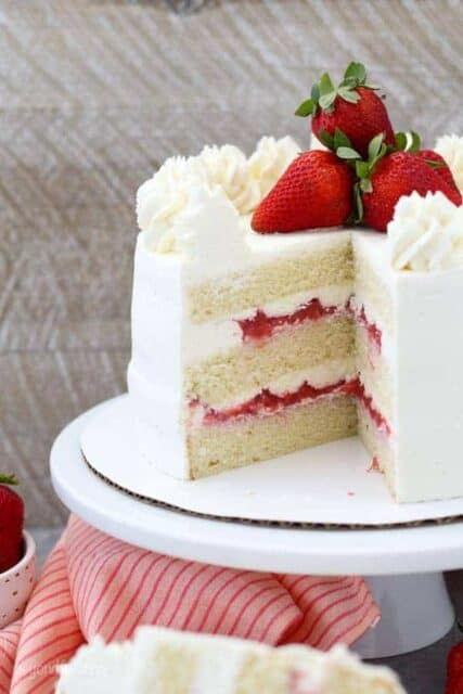 A layered strawberry cake on a white cake plate. The is a big slice missing, showing the inside of the cake and layers of strawberry filling, vanilla cake and frosting.